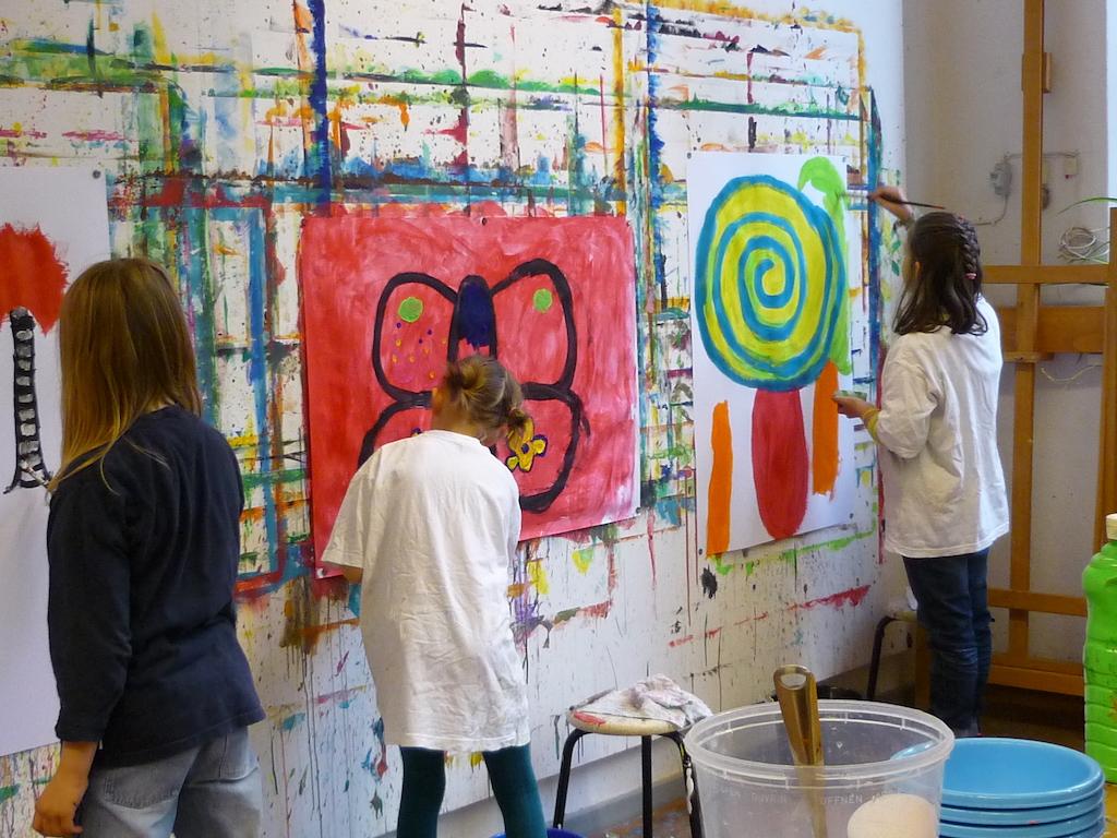 Kinder malen auf großen Formaten an der Malwand